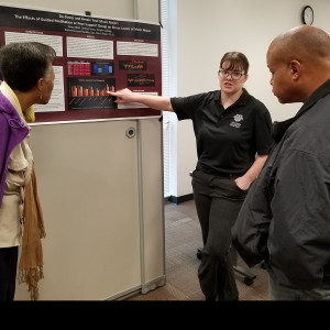 Katherine Buckler talks with staff members Tina Marsh and Derrick Webb about her research on the benefit of meditation.