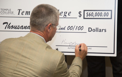 Harry Macy signs a check representing the Temple Industrial Foundation's $60,000 grant to support a social worker position at Temple College.