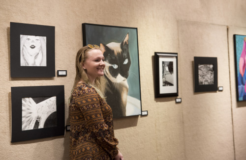 Art student Mylani Peach stands by the picture of her cat she painted for the Spring Student Art ...