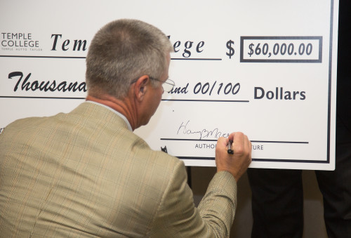 Harry Macy signs a check representing the Temple Industrial Foundation's $60,000 grant to support...